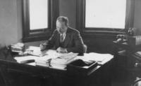 Barton Sits at Desk Writing