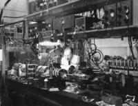 Alan White working in a laboratory with a helium neon laser