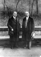 Archie Worthing (right) and an unknown man stand outdoors by a bench in a park
